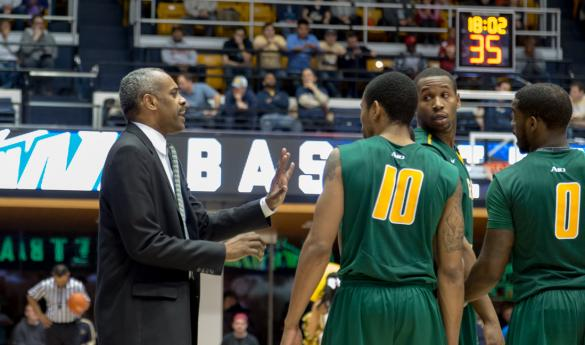 Hewitt has a quick chat with a trio of his players during a game vs. George Washington (photo by Maurice C. Jones).